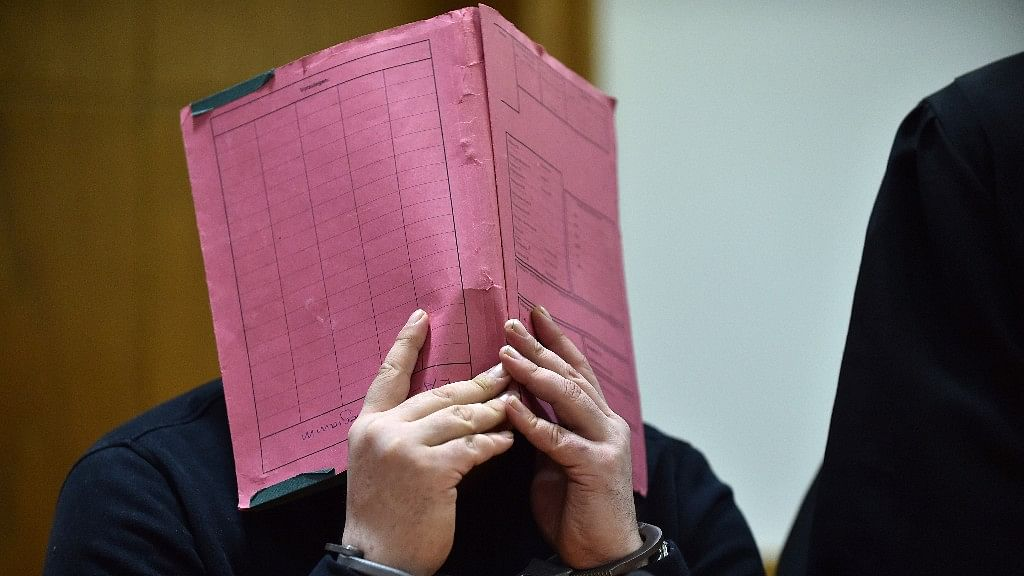 File photo shows former nurse Niels H covering his face during his trial at the regional court in in Oldenburg, northern Germany.