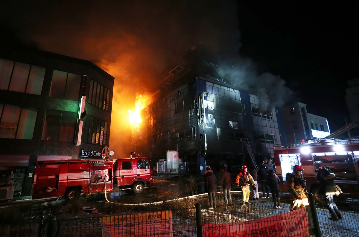 <p>Firefighters try to extinguish a fire at an eight-floor building in Jecheon, South Korea.&nbsp;</p>