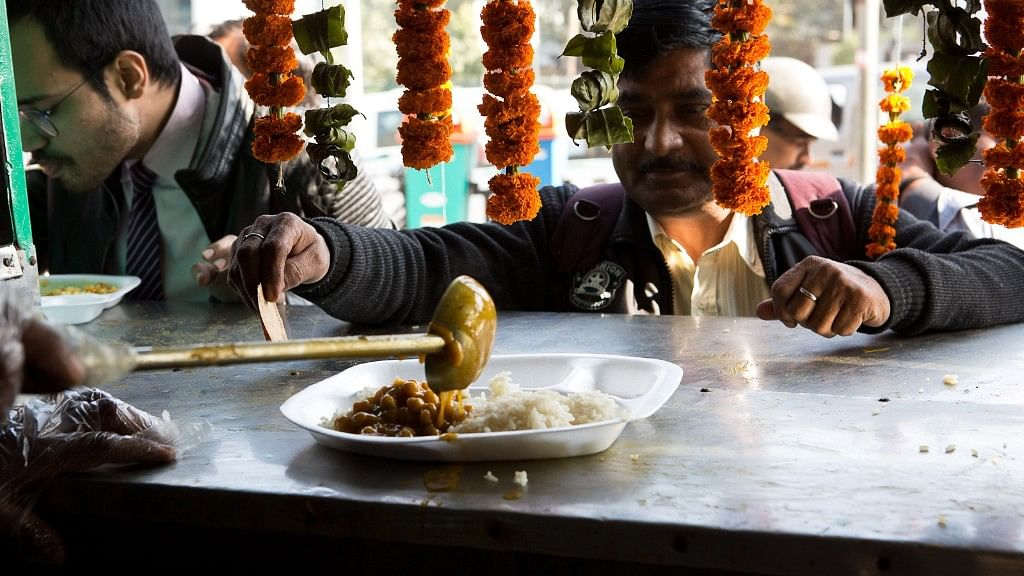 A man waits for rice and chickpeas to be served at the Rs 10 Jan Aahar scheme stall.