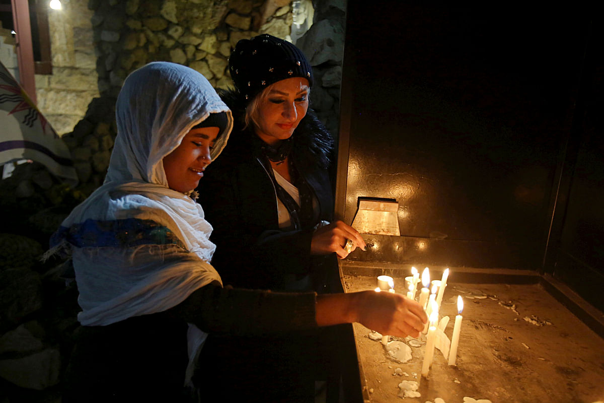 Iraqi Christians light candles after a Christmas Eve Mass in St. Joseph's Church in Baghdad, Iraq, 24 December 2017