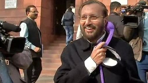 <p>Prakash Javadekar talking into a purple receiver which is connected to his cell-phone.</p>