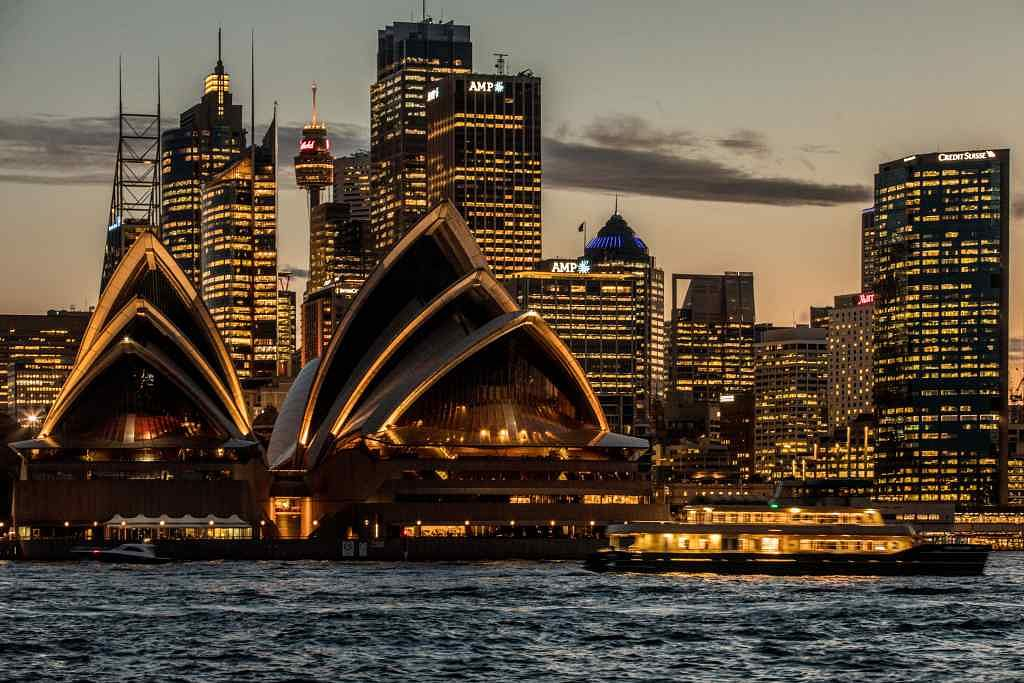 The Sydney Opera House, foreground, and buildings in the financial district stand illuminated at dusk in Sydney, Australia.