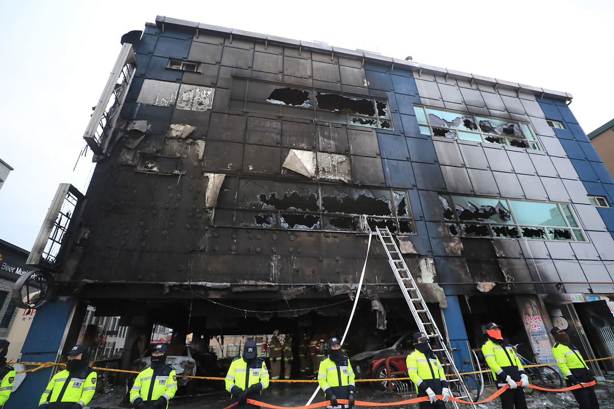 <p>Police officers stand guard in front of a damaged building after a fire in Jecheon, South Korea.</p>