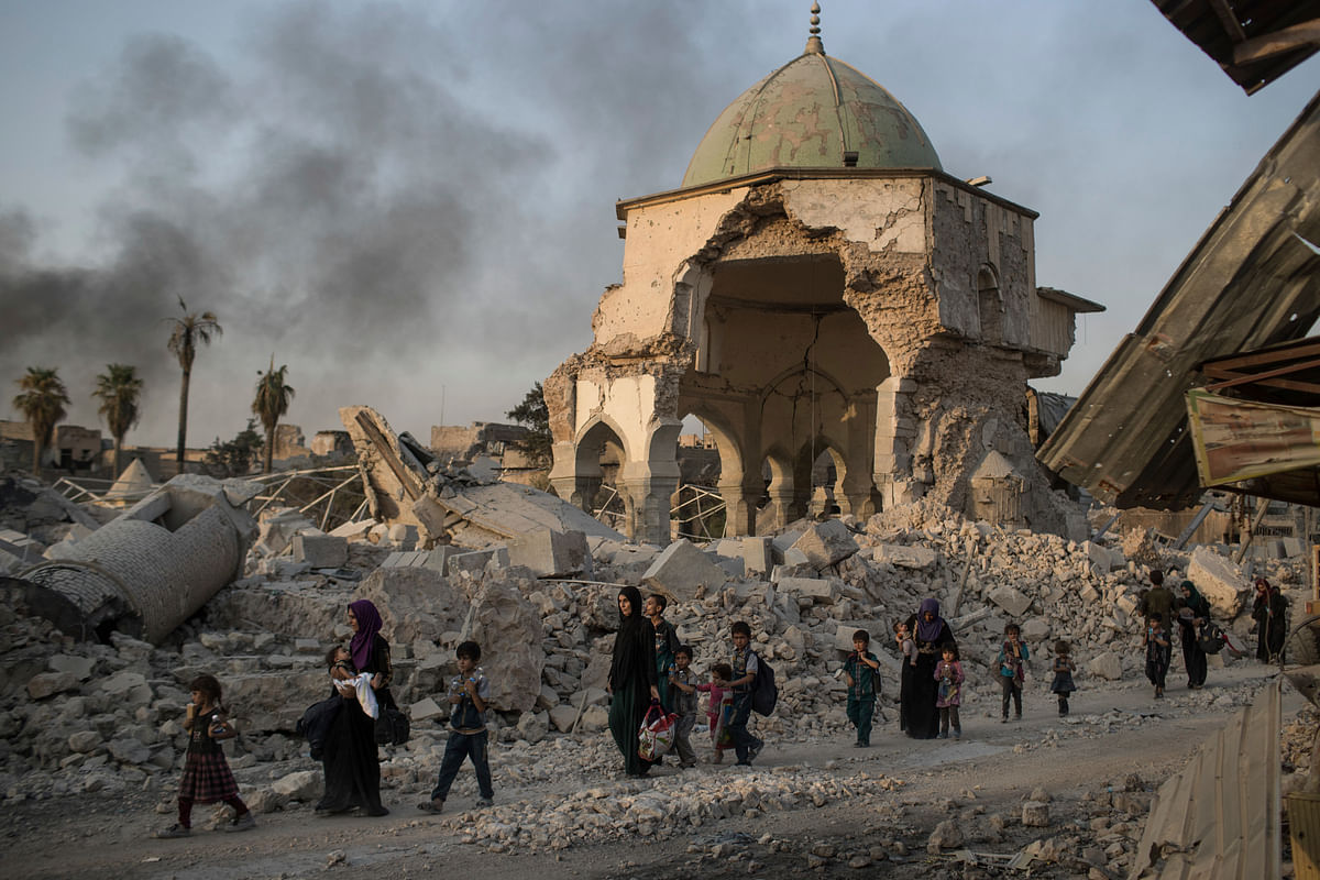 Iraqi civilians walk past the destroyed al-Nuri mosque as Iraqi forces continue their advance against ISIS militants in Mosul, in this file photo from 4 July 2017.