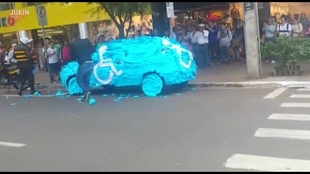 After a man parked his car in the disabled parking area, his car gets covered with blue and white post-it notes.