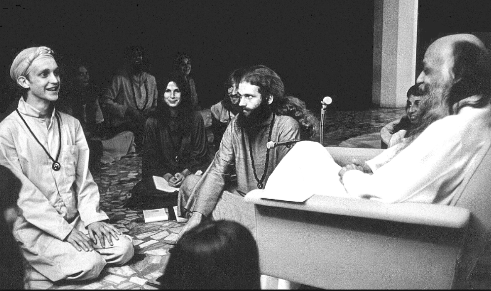 A photo of Osho with his disciples in <i>darshan</i> at Poona in 1977.