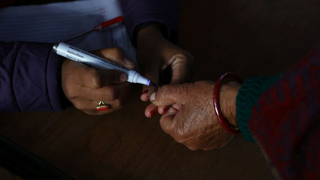 A woman gets her thumb inked to cast her vote.