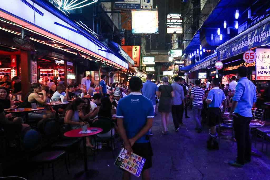 An employee, centre, stands between bars at night in the Silom area of Bangkok, Thailand.