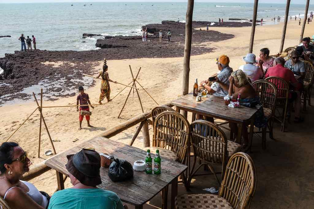 Tourists and visitors sit in a restaurant as children perform at Anjuna beach in Anjuna, Goa.