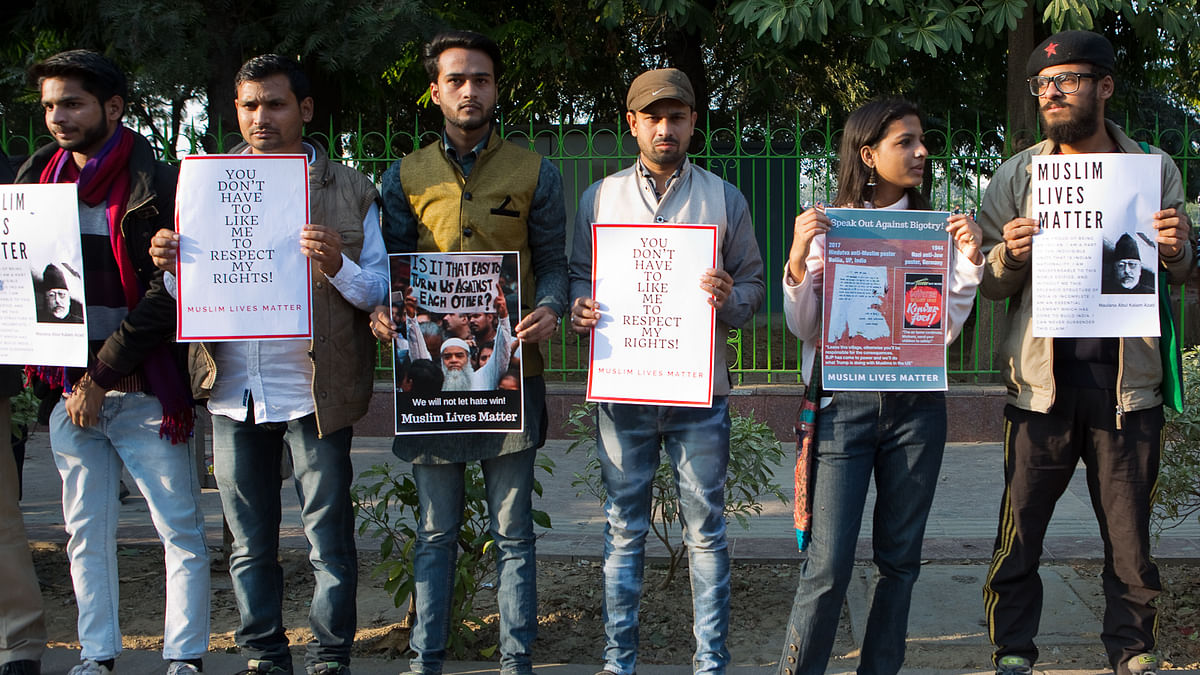 People hold placards at the Muslim Lives Matter protest in CP, New Delhi.