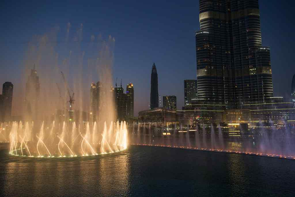 Lights illuminate a water fountain show outside the Dubai Mall at the base of the Burj Khalifa tower, right, in Dubai
