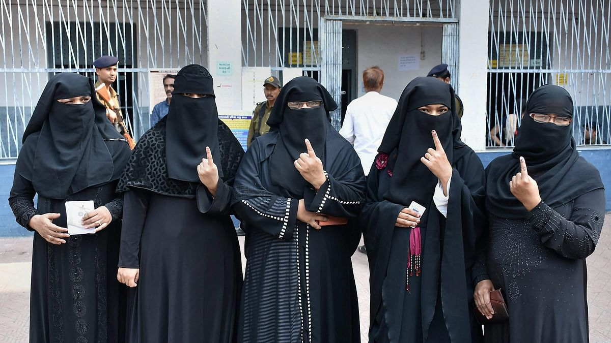 Muslim voters showing their inked fingers at a polling booth during Gujarat Assembly election in Surat.