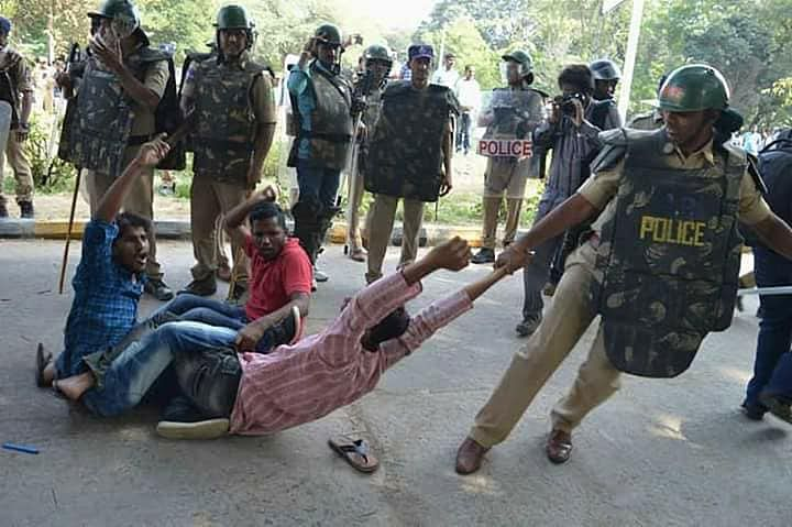 Police personnel dragging the students as they protest.