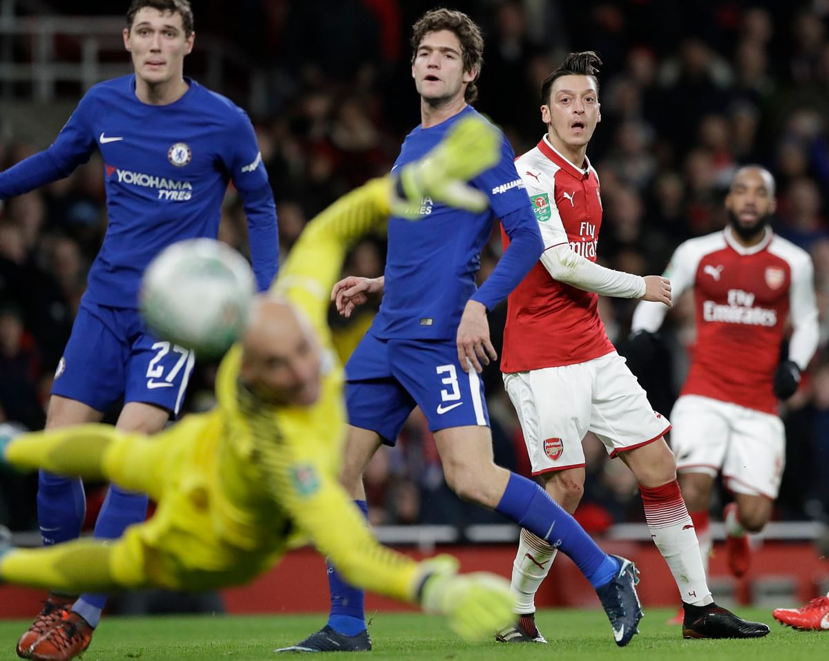 Arsenal's Mesut Ozil (right) shoots during the English League Cup semifinal second leg match against Chelsea  at the Emirates stadium.
