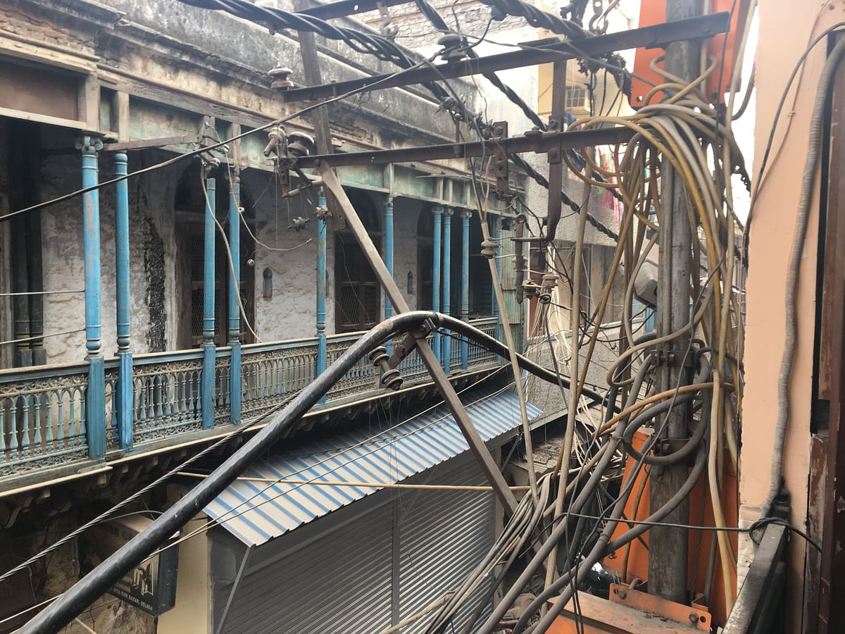 A stack of electricity wires hang dangerously close to the balcony of a residence in Old Delhi.