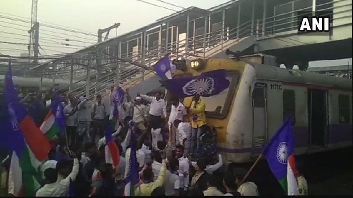 Protesters stop a train at Thane railway station.