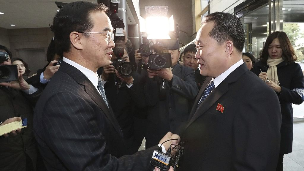 South Korean Unification Minister Cho Myoung-gyon (L), shakes hands with the head of North Korean delegation Ri Son Gwon before their meeting at the Panmunjom, on 9 January.