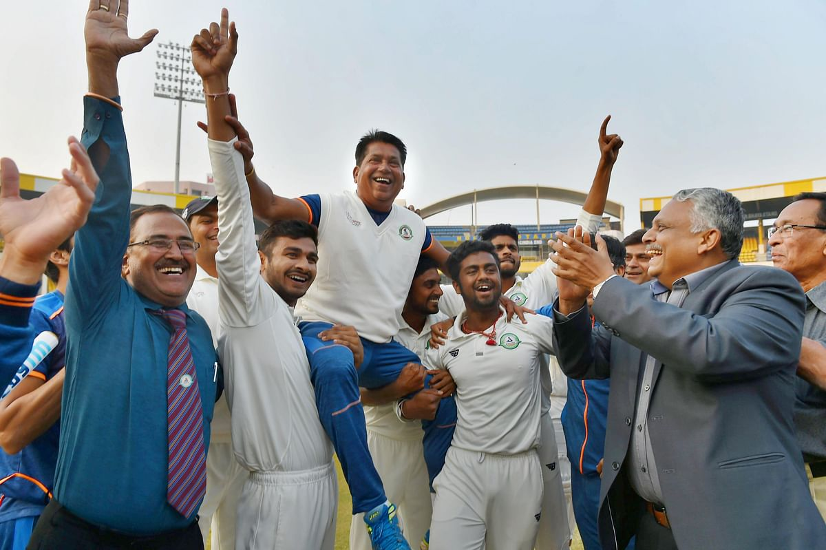 Vidarbha players celebrate with their coach Chandrakant Pandit after winning the Ranji Trophy final cricket match against Delhi by 9 wickets