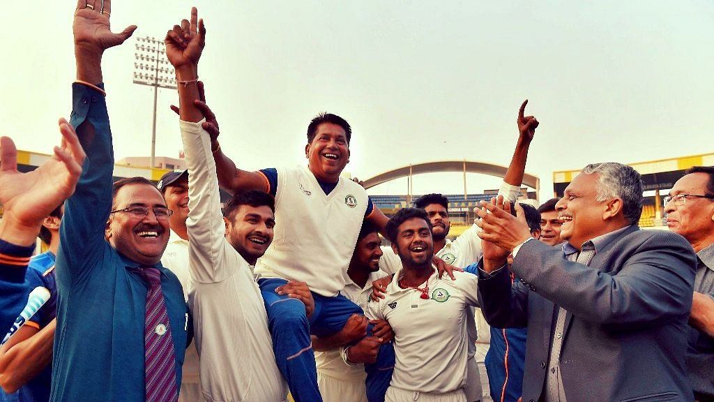 Vidarbha players celebrate with their coach Chandrakant Pandit after winning the Ranji Trophy final cricket match against Delhi by 9 wickets.
