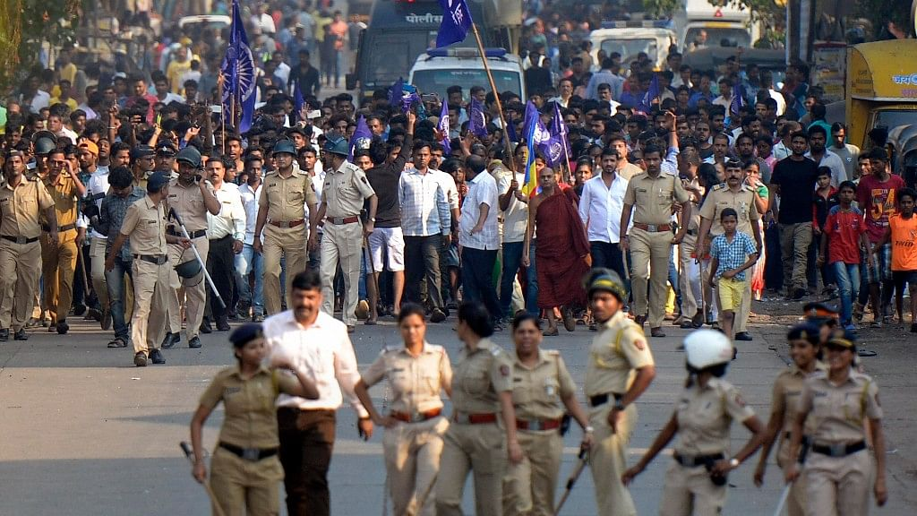 Police accompany protesters as they stage a demonstration  in Mumbai against the violence in Pune's Bhima Koregaon.