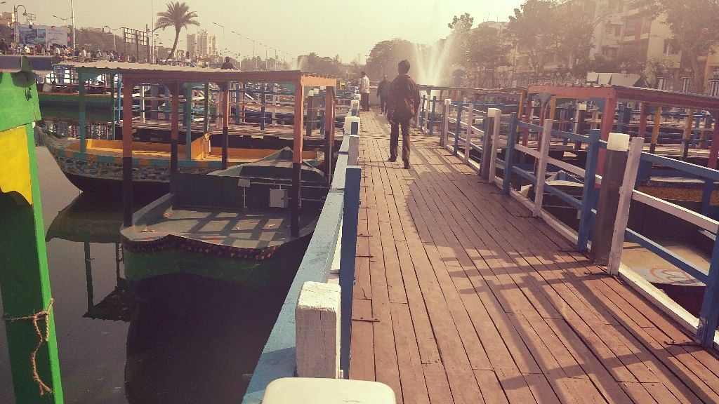 People use a wooden walkway to access the boats.