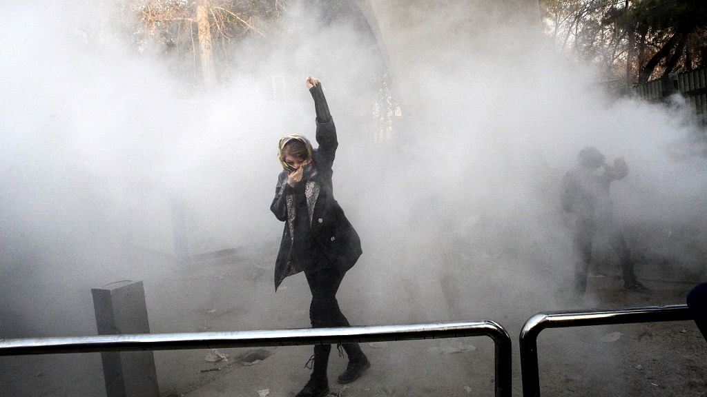 In this photo taken by an individual not employed by the Associated Press and obtained by the AP outside Iran, a university student attends a protest inside Tehran University while a smoke grenade is thrown by anti-riot Iranian police.