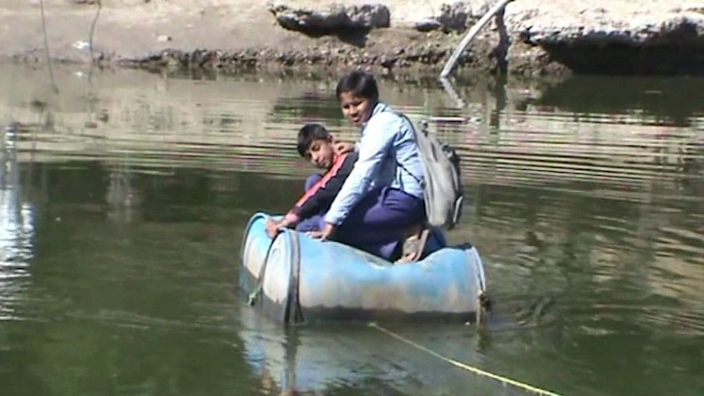 Students at Tungni village in Madhya Pradesh use 'boats' made of drums to cross the river and go to school.