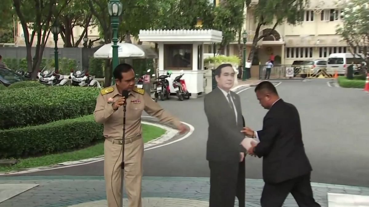 Thailand's Prime Minister Prayuth Chan-ocha, left, directs the scene as a life-size cardboard cut-out figure of himself is carried into view by an aid in Bangkok.