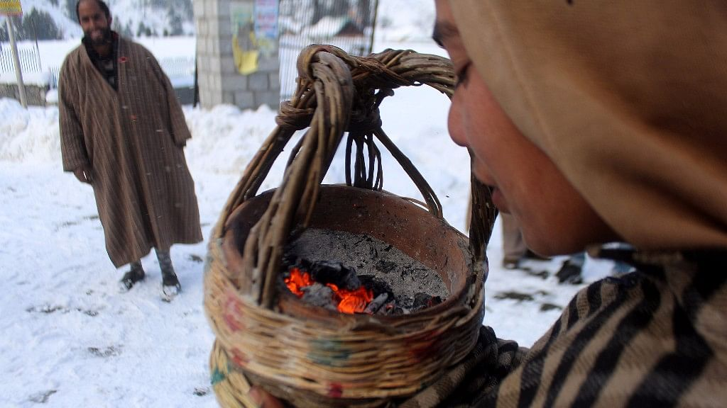 A boy blows a <i>kangri –</i> the traditional fire pot used by Kashmiris during winter to keep themselves warm.&nbsp;