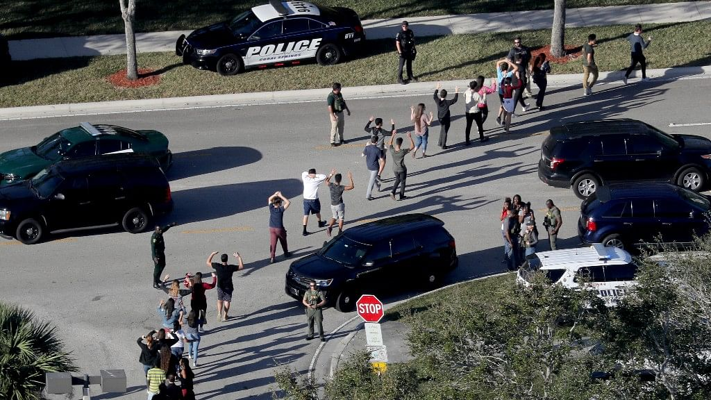 Students hold their hands in the air as they are evacuated by police from Marjory Stoneman Douglas High School in Parkland, Florida, after a shooter opened fire on the campus on 14 February, 2018.