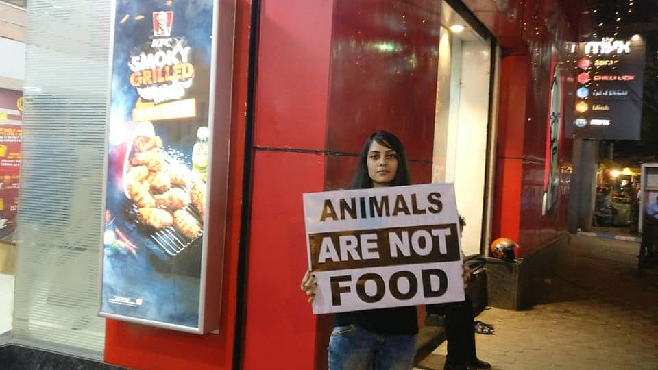 A volunteer holding a placard during the protest in front of KFC, Park Street in Kolkata.