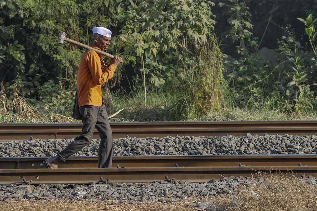 A worker carries a sledgehammer as he walks along rail tracks in Mumbai.