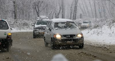 Srinagar: Vehicles move through the snow-covered streets during snowfall in Srinagar on Feb 12, 2018. Moderate to heavy snowfall started in the valley as rain lashed the plains on Monday breaking the nearly two-month long dry spell in Jammu and Kashmir. (Photo: IANS)
