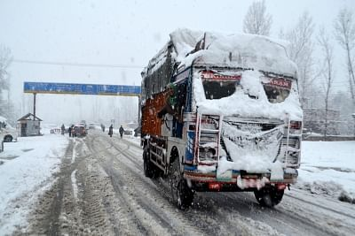 Qazigund: A truck driver enjoys the snowfall even as vehicular movement was affected after the Jammu-Srinagar highway was closed due to heavy snowfall; in Qazigund of Jammu and Kashmir