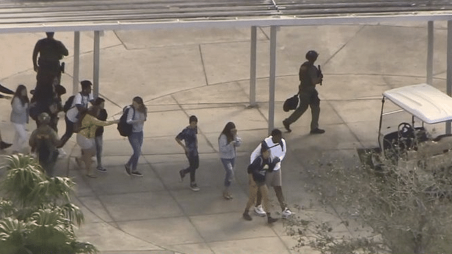 Live television showed dozens of students running and walking away from the school, weaving their way between large numbers of emergency vehicles including police cars, ambulances and fire trucks.