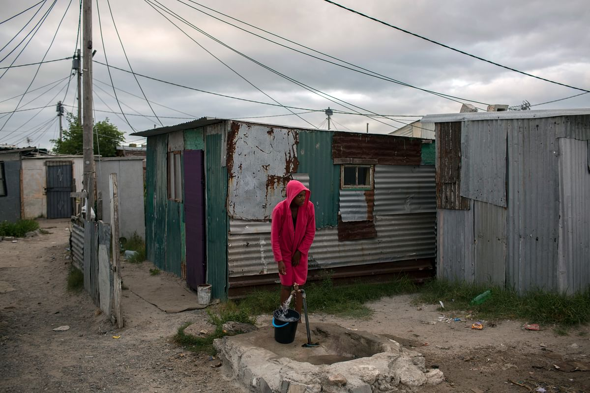 A woman collects water in a settlement near Cape Town.