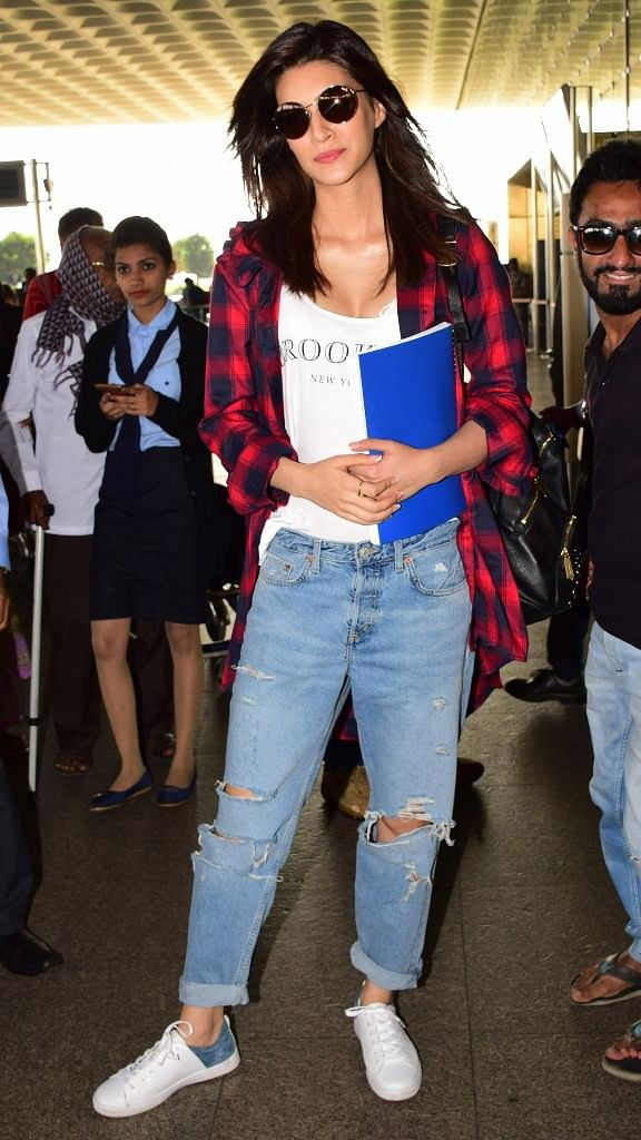 Kriti Sanon the style icon of Bollywood was spotted in a funky look with a classy touch. The ripped jeans paired with the white tank top and the checks shirt can never go out of fashion. Kriti fled to Chandigarh to start her new project <i>Arjun Patiala.</i>