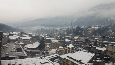 Manali: A view of Manali after fresh snowfall covers roof of houses and the tree-covered mountains on Feb 12, 2018. (Photo: IANS)