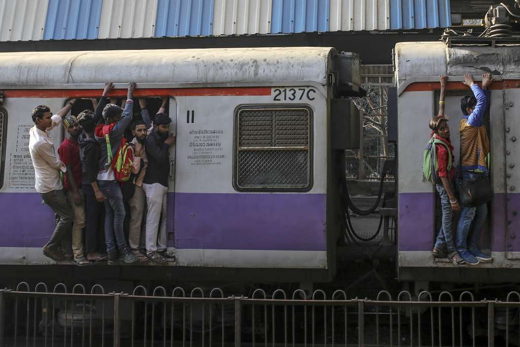 Passengers stand in the doorway, left, and on the side of train carriages as they travel by rail in Mumbai.