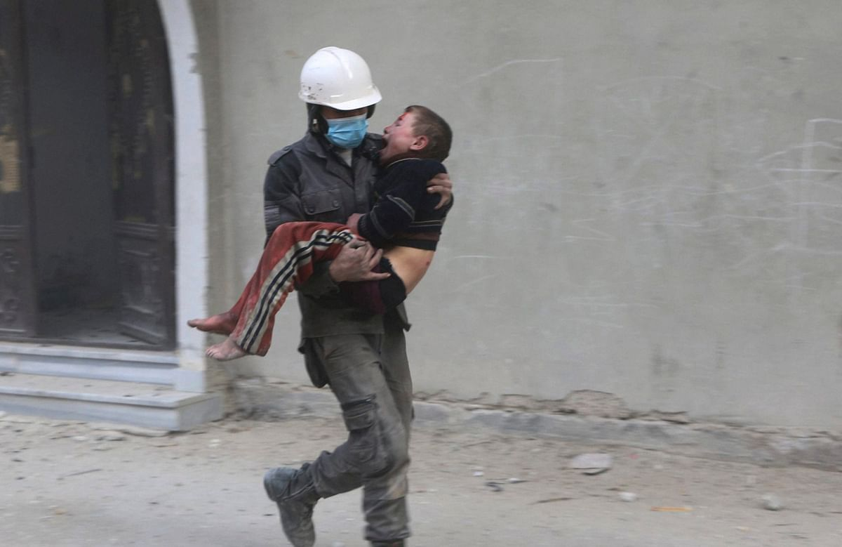 A member of Syrian Civil Defense group, the White Helmets, carries a boy who was wounded during airstrikes and shelling by Syrian government forces, in Ghouta,  Syria.