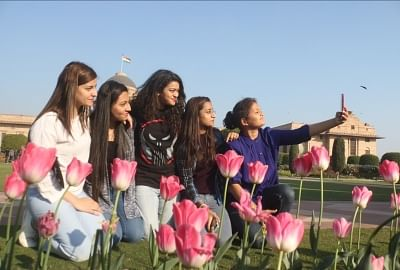 New Delhi: Girls pose for selfies beside pink tulips at the Mughal Gardens of Rashtrapati Bhavan in New Delhi. (Photo: IANS)