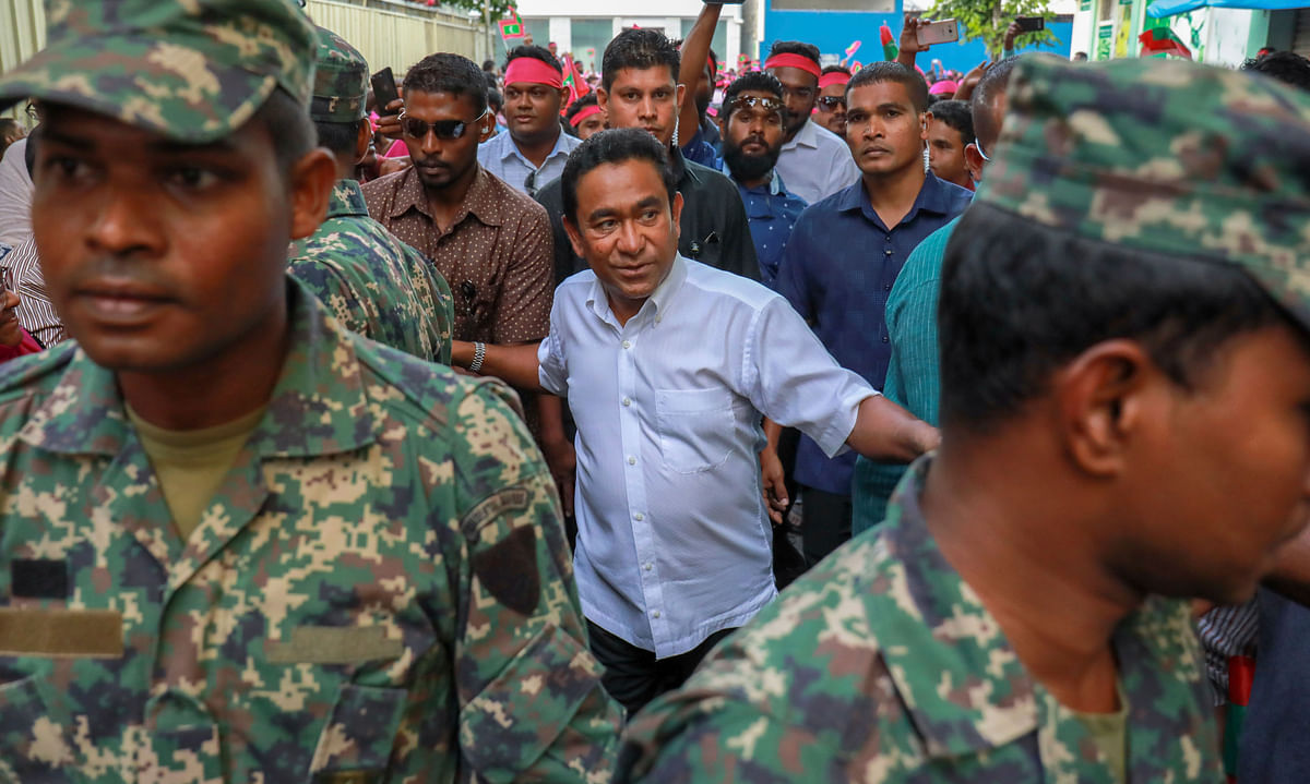 Maldivian President Yameen Abdul Gayoom, center, surrounded by his bodyguards arrives to address his supporters in Male, Maldives.