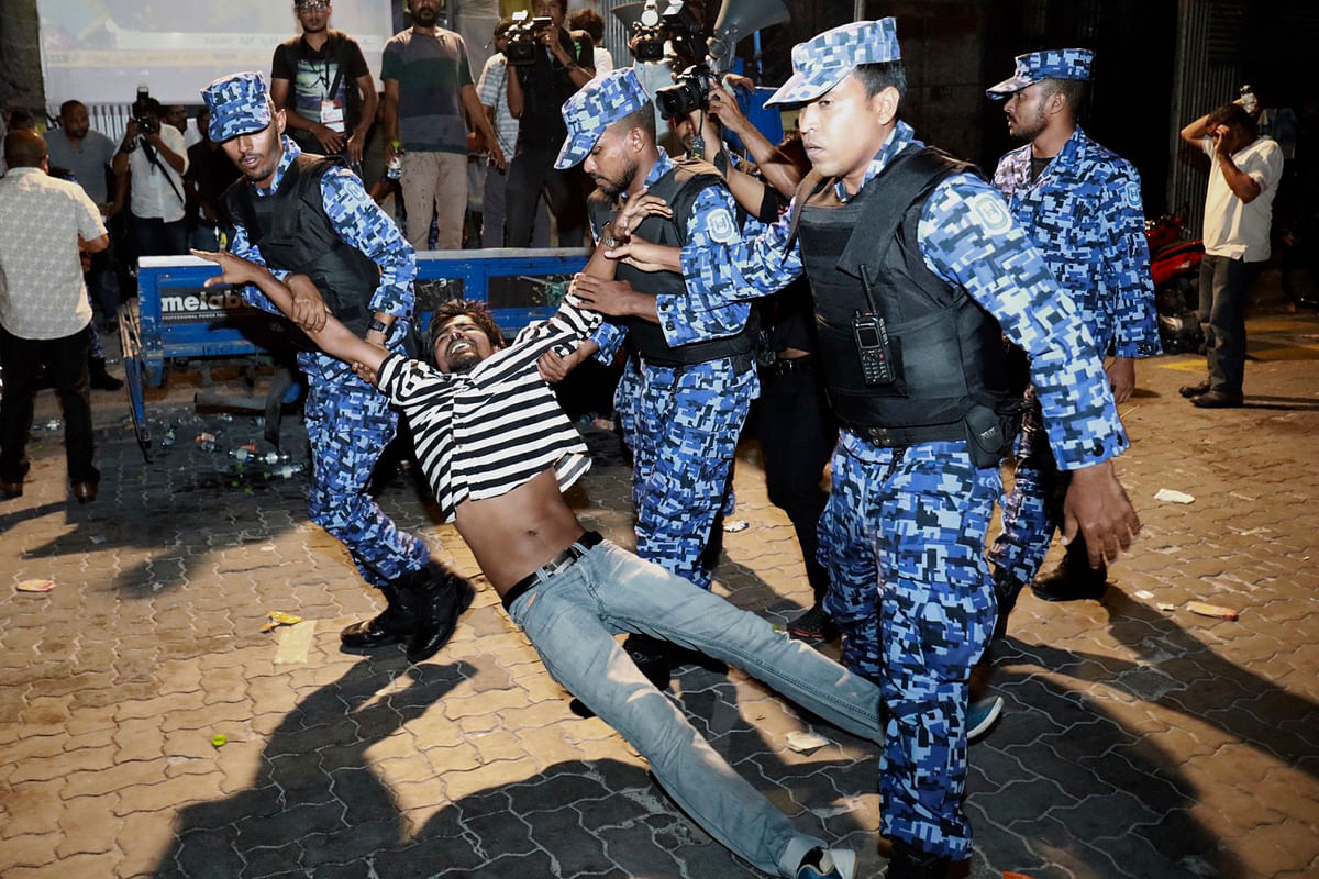 Maldivian police officers detain an opposition protestor.