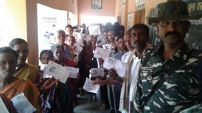 Bargarh: People waiting in queues to cast their votes, show their Voter ID cards during bypoll for Bijepur Assembly constituency in Odisha