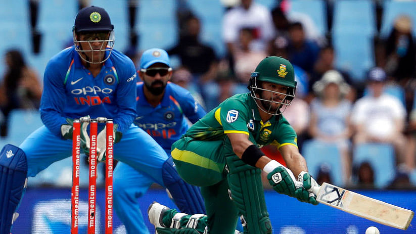 JP Duminy plays a sweep shot as MS Dhoni looks on.