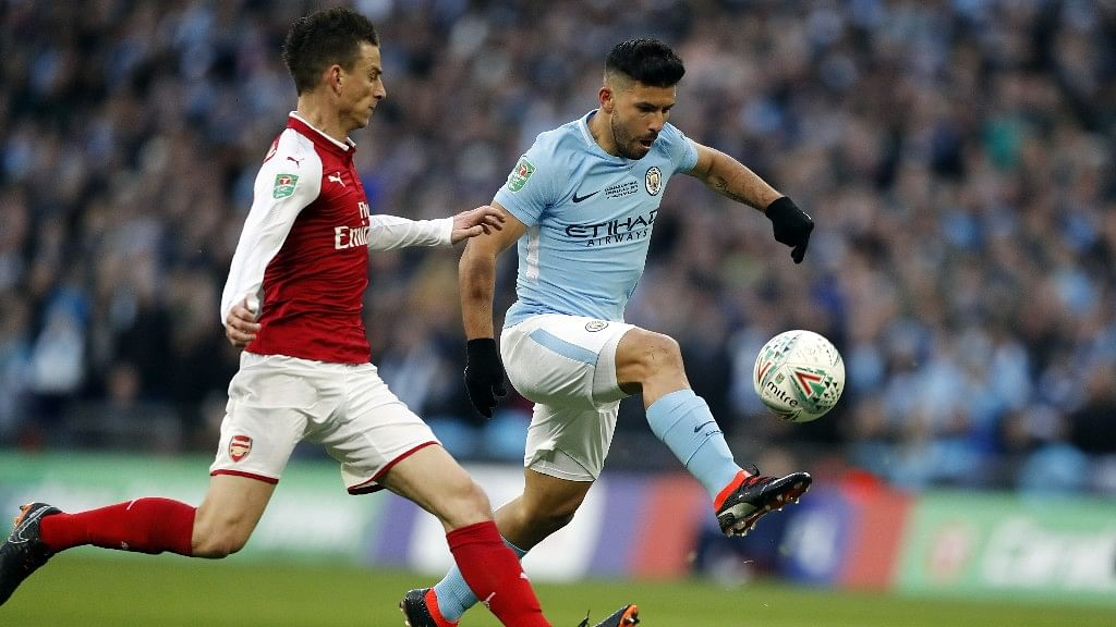 Manchester City's Sergio Aguero (right) scores the opening goal during the English League Cup final soccer match against Arsenal on Sunday.