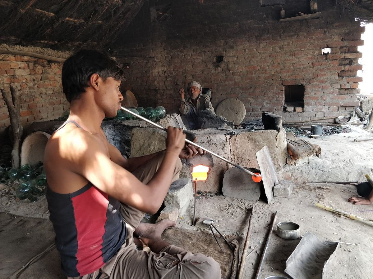 A man is seen blowing into the pipe to make gangajali.
