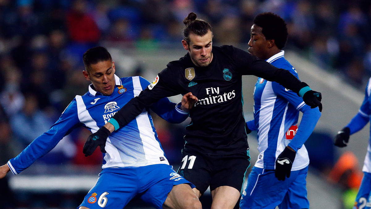 Real Madrid's Gareth Bale, center, vies for the ball with Espanyol Oscar Duarte.