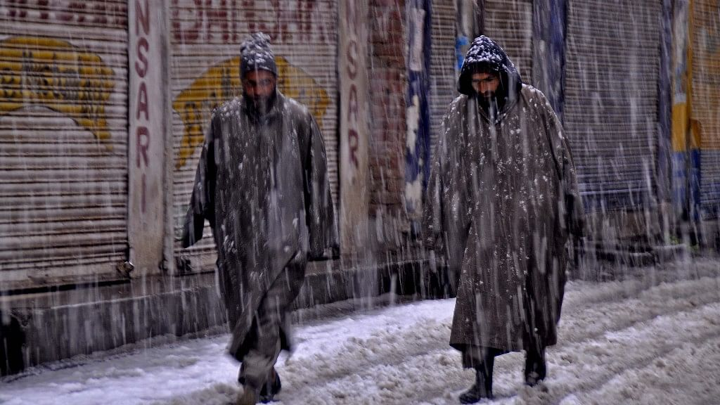 Two men walk in heavy snow in Srinagar.