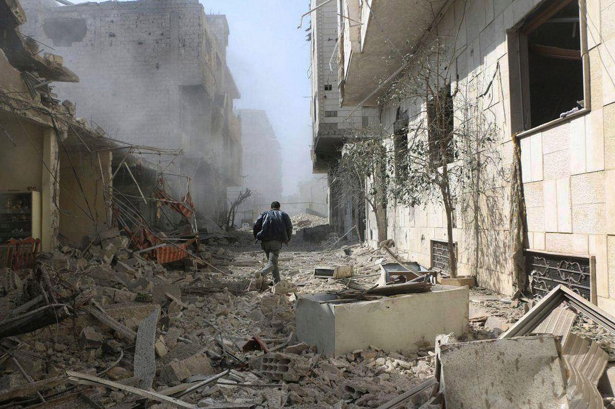 A Syrian man runs between buildings destroyed in airstrikes and shelling by Syrian government forces, in Ghouta, Syria.
